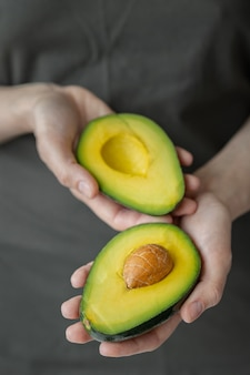 아보카도를 들고 있는 여성의 손, 어두운 티셔츠를 입은 백인 여성, 주방, 요리 셰프, 익고 맛있는 아보카도, 건강하고 건강한 음식, 날 과일과 채소 채식주의자 프리미엄 사진