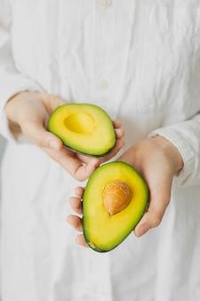 아보카도를 들고 있는 여성의 손, 티셔츠를 입은 백인 여성, 주방, 요리 셰프, 익고 맛있는 아보카도, 건강하고 건강한 음식, 날 과일과 채소 채식주의자 프리미엄 사진