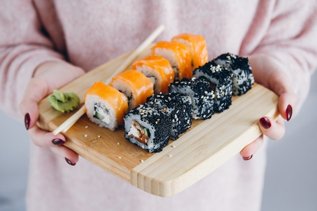 Women's hands holding the board with a philadelphia roll