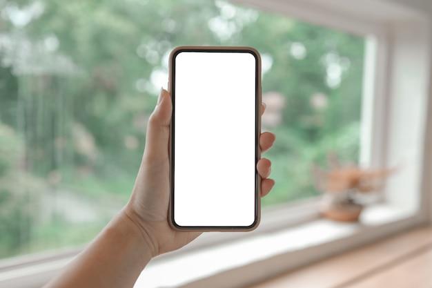 Женские руки, держа экран космоса пустой копией сотового телефона.