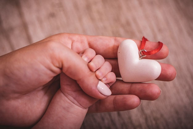 Women's hands holding the child's hand with a heart. world humanitarian day