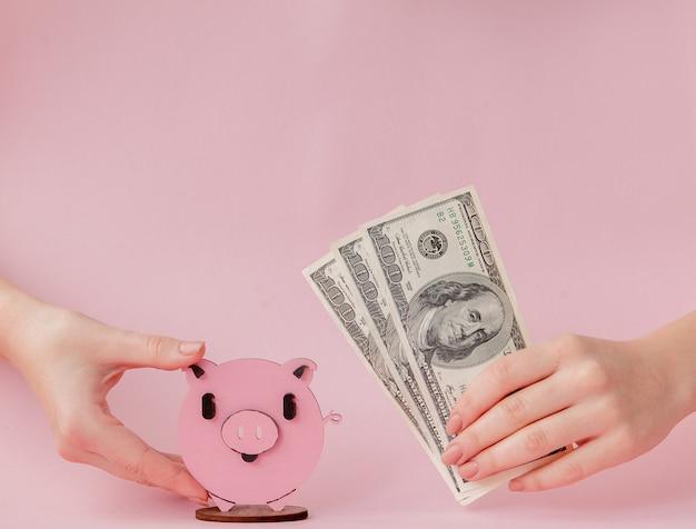 ピンクのpiggybankとドル紙幣を保持している女性の手
