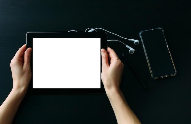 スマートフォンとヘッドフォンが置かれている黒い木製のテーブルに対して空の白い画面でタブレットコンピューターを保持している女性の手。日常生活におけるデジタル技術の使用。