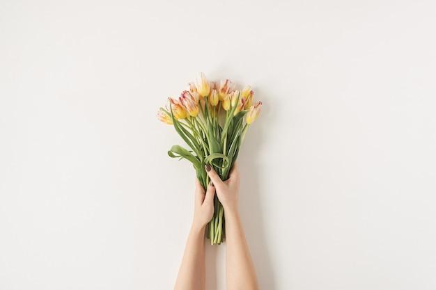 白い壁にチューリップの花の花束を保持している女性の手