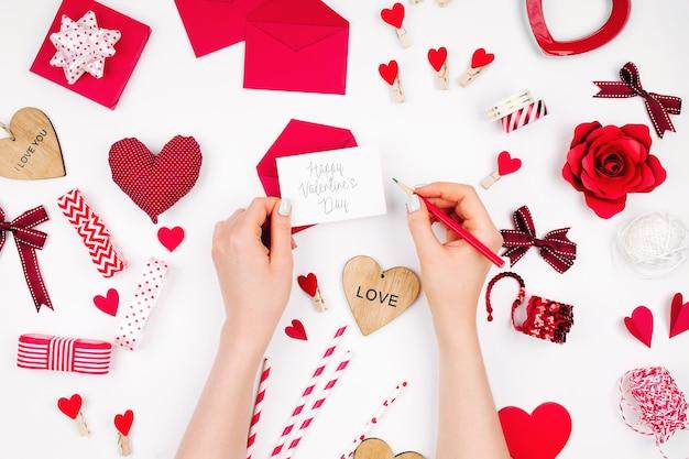ロマンチックな装飾と白い背景の上のバレンタインカードを保持している女性の手。フラットレイアウト