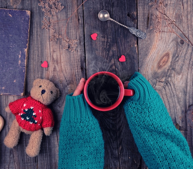 ブラックコーヒーと赤いセラミックマグカップを保持している緑のニットセーターで女性の手