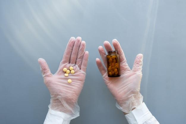 医療用手袋をはめた女性の手は、錠剤のガラス瓶を持っています。青い背景。医療医師の概念。
