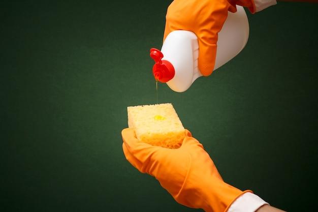 緑の背景に食器洗い液とスポンジのボトルとオレンジ色の保護手袋の女性の手。洗濯と掃除のコンセプト。