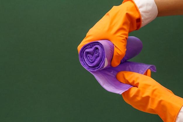 緑の背景にゴミ袋とオレンジ色の保護手袋の女性の手。洗濯と掃除のコンセプト。