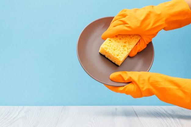 青い背景にプレートとスポンジが付いているオレンジ色の保護手袋の女性の手。洗濯と掃除のコンセプト。