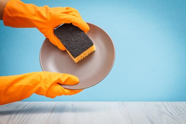灰色と青の背景にプレートとスポンジが付いているオレンジ色の保護手袋の女性の手。洗濯と掃除のコンセプト。