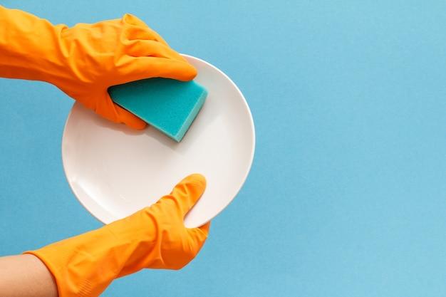 青い背景にプレートとスポンジが付いているオレンジ色のゴム手袋の女性の手。洗濯と掃除のコンセプト。
