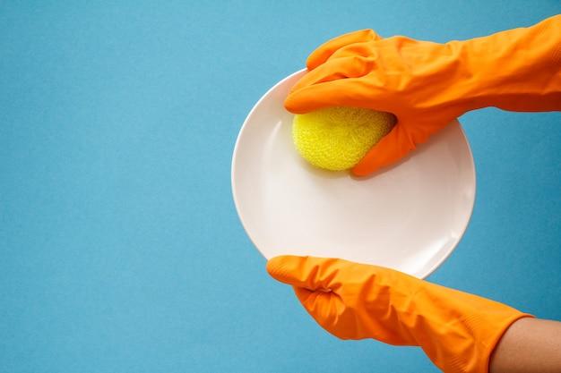 白いプレートと青い背景に黄色のスポンジとオレンジ色のゴム手袋の女性の手。洗濯と掃除のコンセプト。