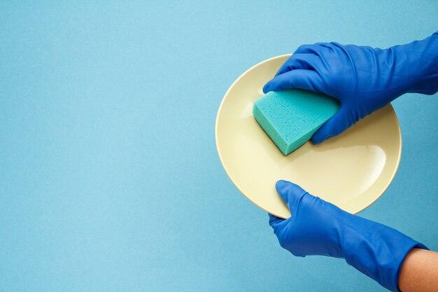 青の背景にベージュのプレートとスポンジが付いている保護手袋の女性の手。洗濯と掃除のコンセプト。