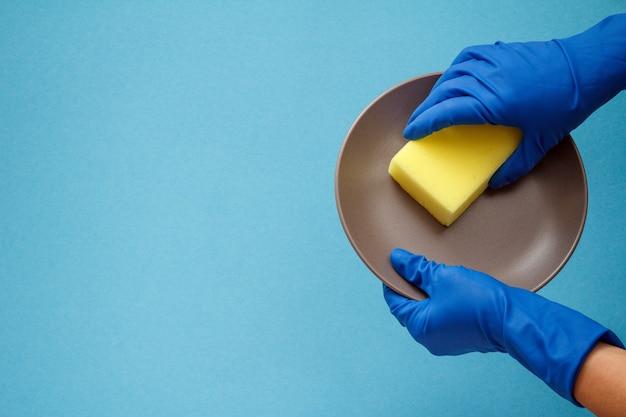 青い背景に茶色のプレートと黄色のスポンジが付いている保護手袋の女性の手。洗濯と掃除のコンセプト。