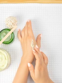 白いタオルの上にクリームとナチュラルクリームの瓶を広げる過程の女性の手。手は自然化粧品の女性を開花させ、女性の手は彼女の肌に保湿クリームを適用します