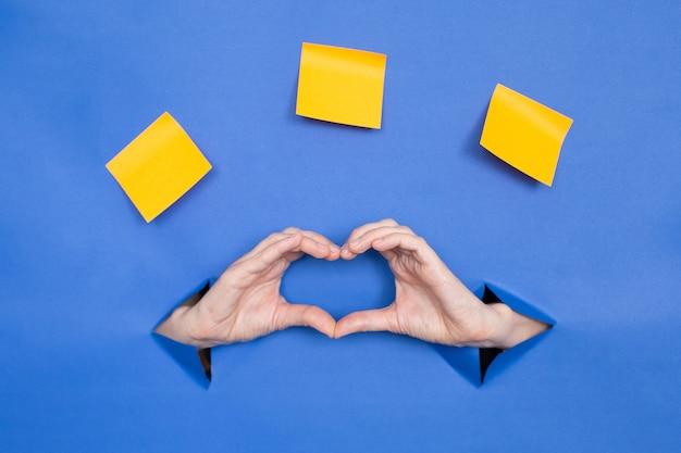Женские руки в форме сердца на синем фоне. женские вставлены в бумажный фон, сверху три бумажные палочки. место для надписи.