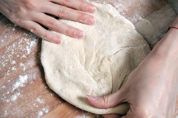 Женские руки замешивают тесто из пшеничной муки