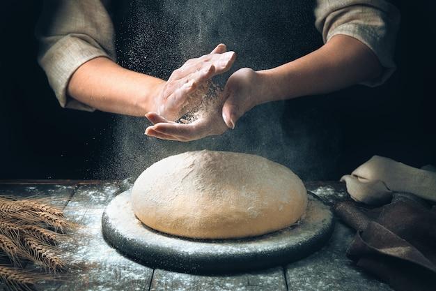 여성의 손이 반죽을 반죽하여 빵을 만듭니다.