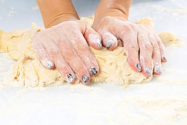 여성의 손은 밝은 배경에 반죽을 반죽합니다. 요리와 베이킹.
