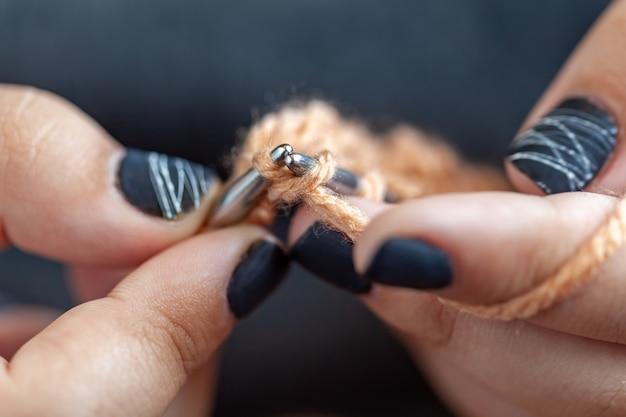 Женские руки вяжут из разноцветной шерсти. ручное вязание