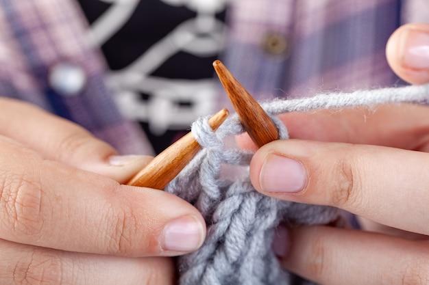 Женские руки вяжутся из серой шерсти.
