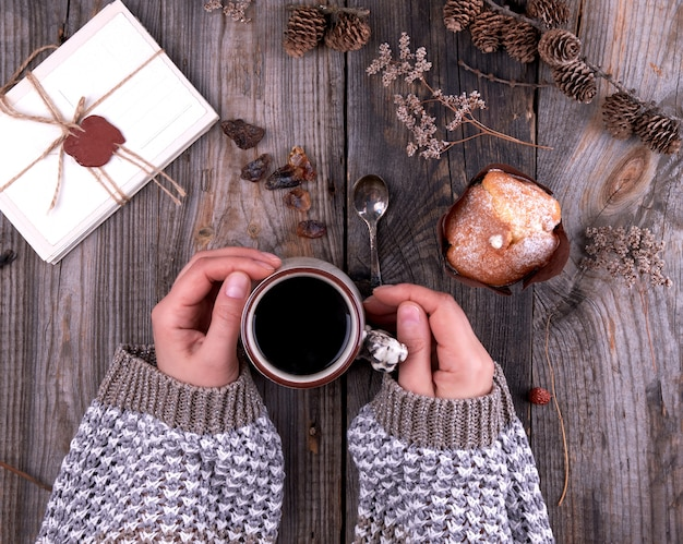Women's hands in a knitted brown sweater holding a ceramic mug with black coffee