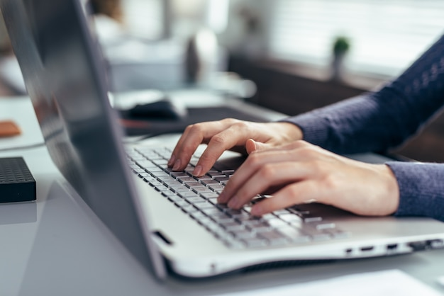 Women's hands on a laptop keyboard close-up.