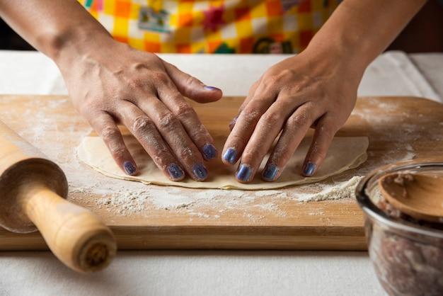 Женские руки лепят тесто для азербайджанского блюда гутаб.