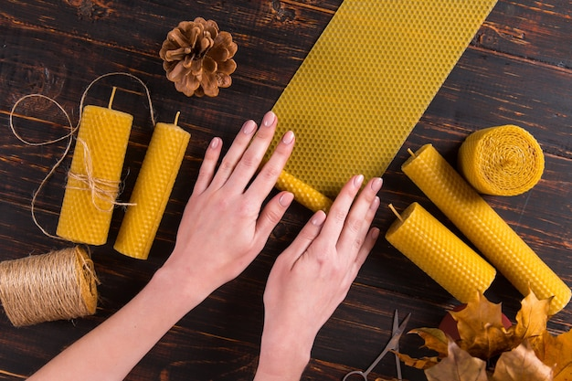 Women's hands make handmade candles of natural wax with texture of honeycomb bees, on a wooden table.