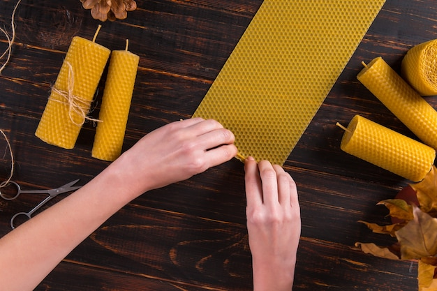 Женские руки лепят свечи из натурального воска с текстурой пчелиного соты на деревянном столе.