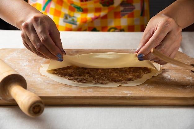나무 보드에 아제르바이잔 요리 gutab를 만드는 여자의 손.
