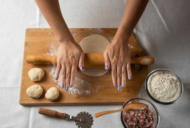 Mani delle donne che fanno la preparazione per il gutab del piatto azerbaigiano.