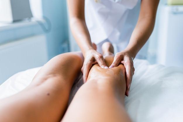 여자의 손은 경기 후 선수의 다리와 정강이를 마사지합니다. 스포츠 마사지, 회복.