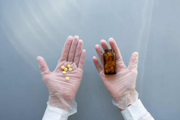 Women's hands in medical gloves hold a glass jar of pills. blue background. healthcare medical doctor concept.