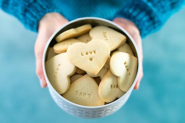 Женские руки предлагают коробку печенья в форме сердца с любовными буквами