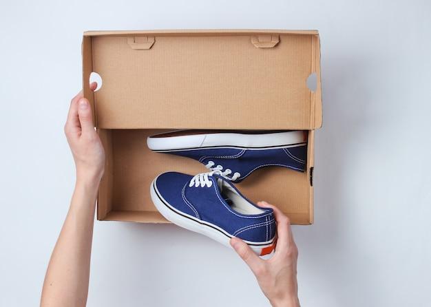女性の手は新しいスタイリッシュなスニーカーをグレーにした段ボール箱を開きます。上面図