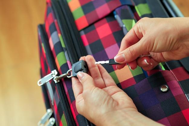 Женские руки открывают чемодан с вещами. концепция путешествия