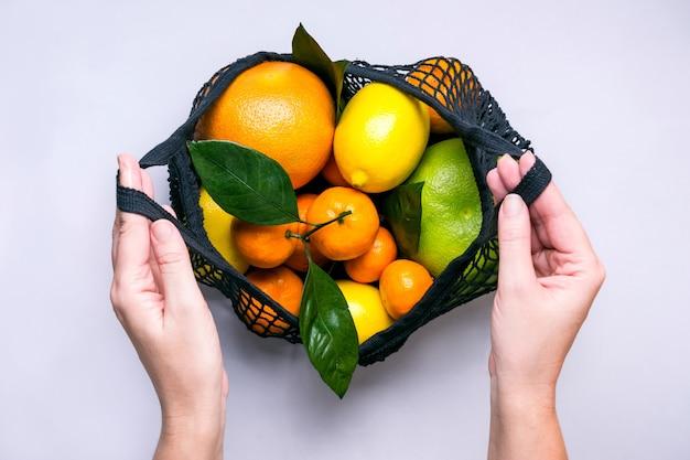 여성의 손은 다채로운 감귤류 과일이 있는 검은색 직물 가방을 엽니다. 건강한 음식과 제로 폐기물 개념..