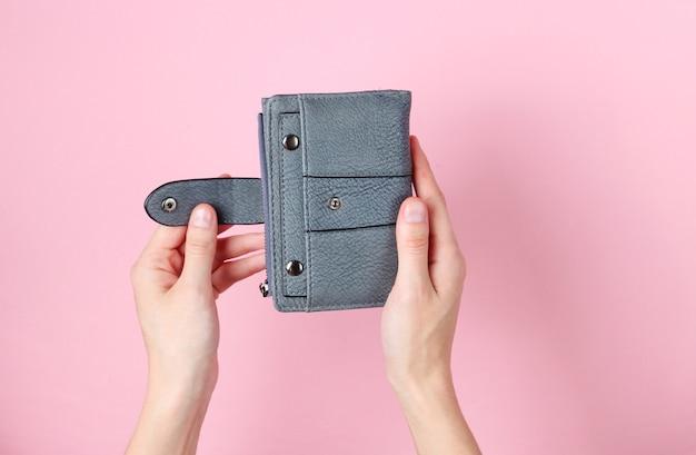 Женские руки открывают кожаный бумажник на розовом.