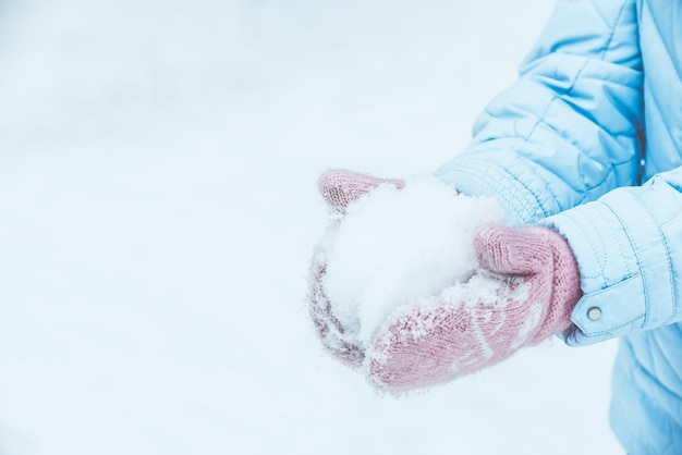 Women's hands in pink mittens make a snowball for outdoor play in the winter in the forest, toned and matte.