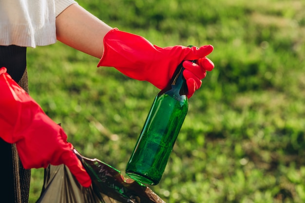Women's hands in red rubber gloves. woman collects trash in the bag. volunteer scavenge garbage in the summer park. girl collects plastic and glass bottles in the package