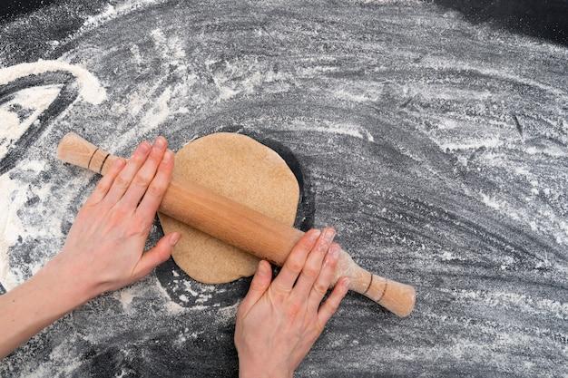 ショートブレッドクッキーの生地を広げる女性の手。自家製ベーキング。