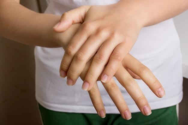 Женские руки смазывают друг друга увлажняющим косметическим кремом