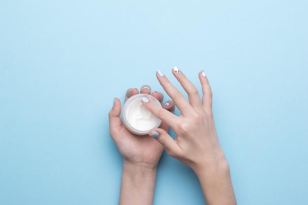 Женские руки берут крем из баночки на синем. уход за кожей рук. плоская планировка.