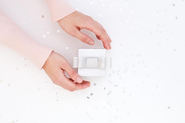 銀のギフトボックスを取る女性の手