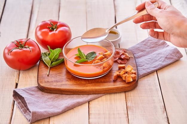 ガスパチョのプレートを味わう女性の手。地中海料理と健康的な食事。