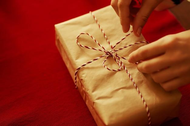 Женские руки завязывают ленточку на подарке на красном фоне