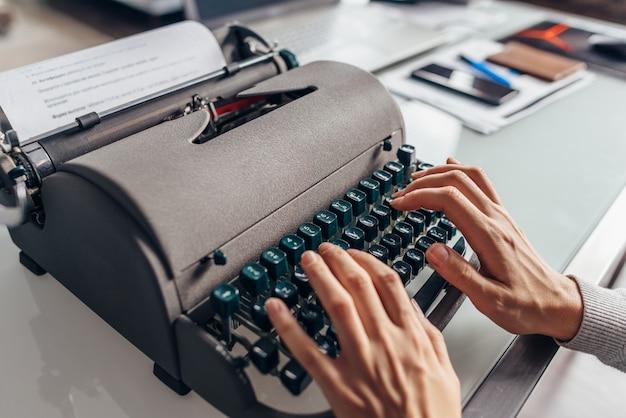 古いタイプライターでタイプする女性の手。