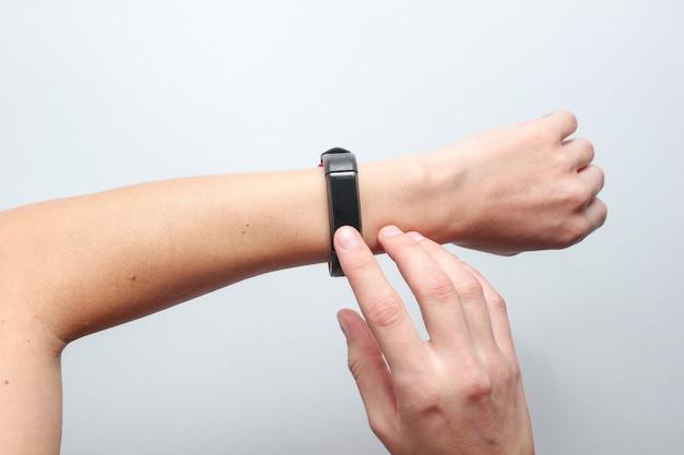 女性の手は灰色のテーブルにスマートな時計を使用しています。モダンなガジェット、トップビュー